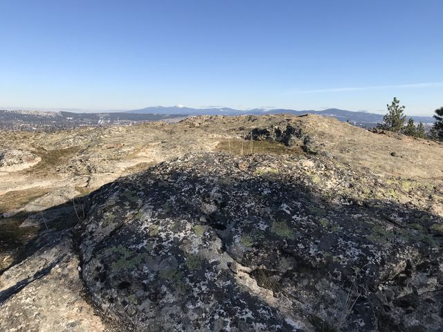 A rocky plateau with views of the Selkirk Mountains in the distance